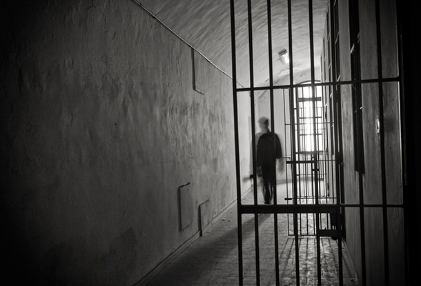 photo illustration: inmate in greyscale cell
