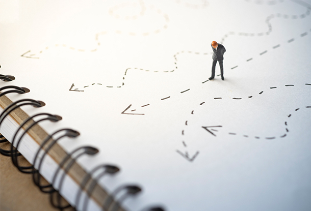 photo: miniature person looking down at lines on a notepad