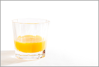 photo: half a glass of orange juice on a plain background (iStockphoto)