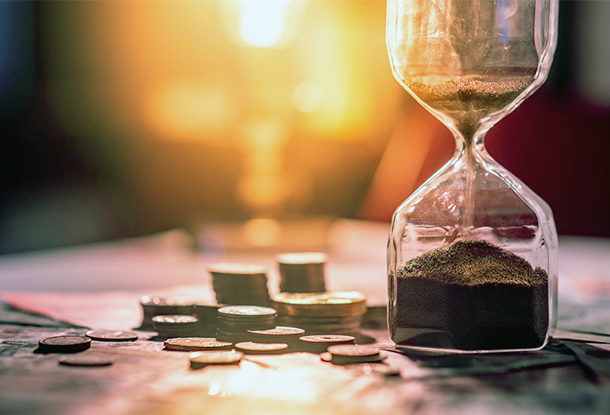 photo: hourglass on table with banknotes and coins (iStockphoto)