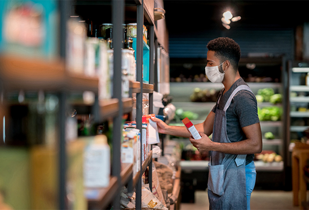 photo: worker wearing mask stocks shelves (iStockphoto)