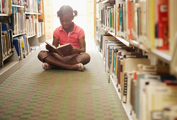 photo: Girl reading at the library (iStockphoto)