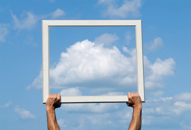 photo: hands holding a frame in front a cloud in the sky (iStockphoto)