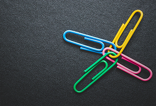 Paper clips on black background, teamwork and success (iStockphoto)