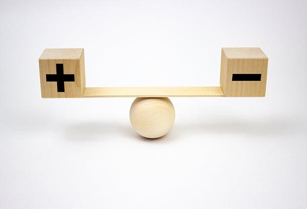 photo: plus and minus blocks balanced on a teeter-totter (iStockphoto)