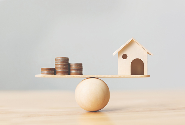 image: Wooden home and money coins stack on wood scale (iStockphoto)