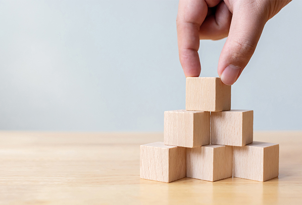 photo: hand with building blocks (iStockphoto)