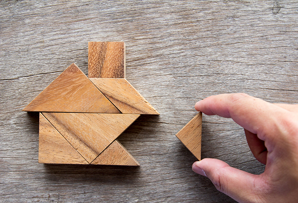 photo: hand completes tangram of a house (iStockphoto)